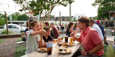Family eating pizza and breadsticks on an outdoor picnic table at Parlour in Jeffersonville, IN