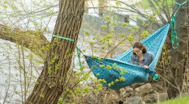 A woman sits in a hammock and reads