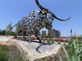 A large bull made from shiny chrome bumper guards stands on a rock slab in Wichita, KS