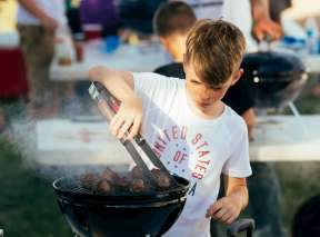 Young boy grilling pork on grill during Derby BBQ & Musical Fest Kid Chef Cookoff Contest