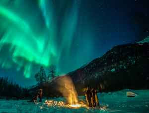 Travelers camp out to catch the northern lights near Anchorage.