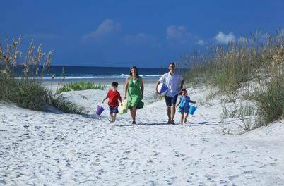 Family walking thru dunes at Wrightsville Beach