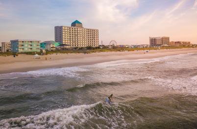 Woman surfing alone at Carolina Beach, NC