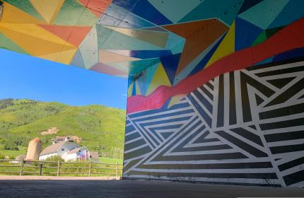 Artists mural in tunnel with the white barn in background