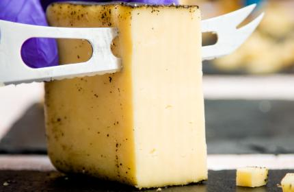 A large piece of cheese getting cut into slices