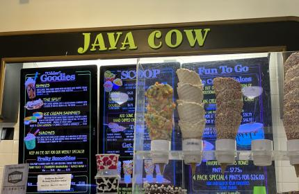 Waffle cones in front of Java Cow sign and menu