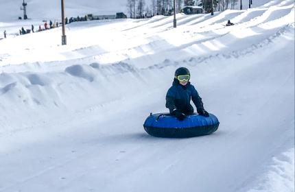 a boy rides a blue tube down a tubing lane in Park City