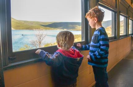 Two boys looking out at a lake from a train car window