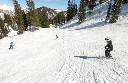 Three kids skiing down a mountain