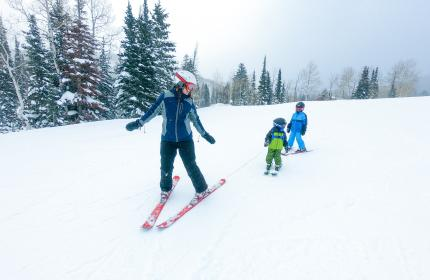 Mother Skiing with her two young kids