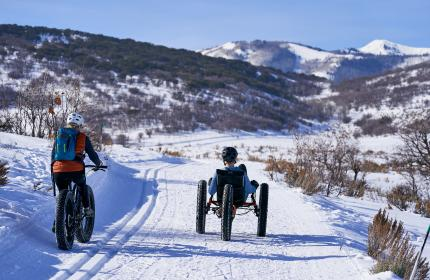 Two people fat tire biking on snow