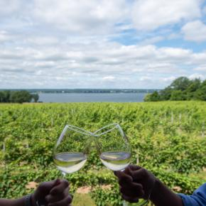 Couple holding wine glasses at Ventosa Winery with lake in background