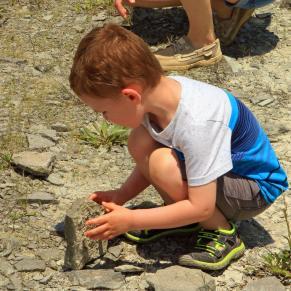 Boy bent down looking at rocks at Caesar Creek Lake