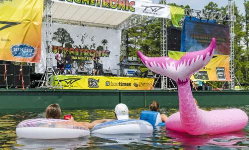 4 people in a lake on floats watching live music