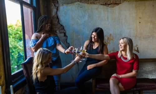 Four women cheering with wine