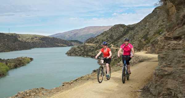 Two women cycling the Roxburgh Gorge Trail alongside Lake Roxburgh