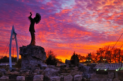 The Keeper of the Plains stands under a beautiful purple and orange sunset in Wichita