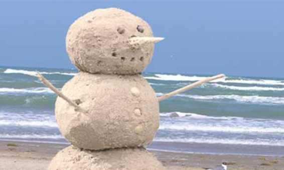 A happy snowman sand sculpture on Daytona Beach.