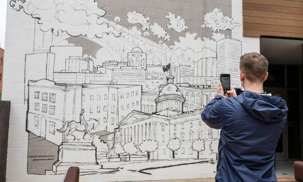 A young man takes a photo of a black and white line drawing mural of Columbia's skyline on his cellphone.