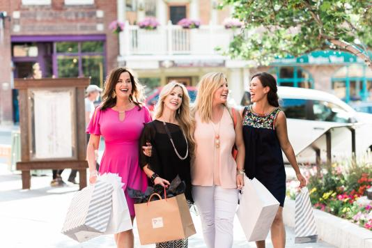 Four women walking on Main Street with shopping bags