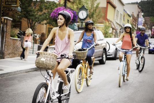 Four adults riding cruiser bikes down Historic Main Street