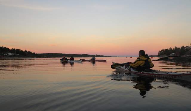 Three kayaks at sea by sunset in Risør
