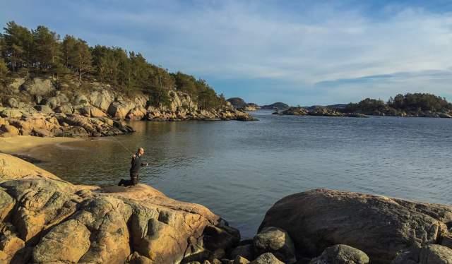 A man fishing on a beach along the sea