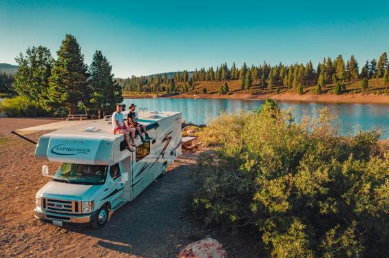 Friends sitting on RV by lake