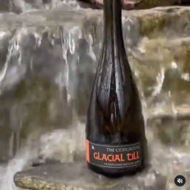 Bottle of Glacial Till with waterfalls in background