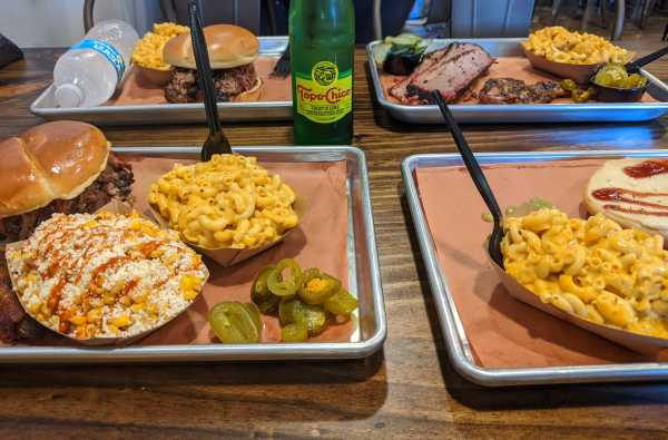 Photo of food trays at Hurtado Barbecue with sandwiches, corn and macaroni and cheese.
