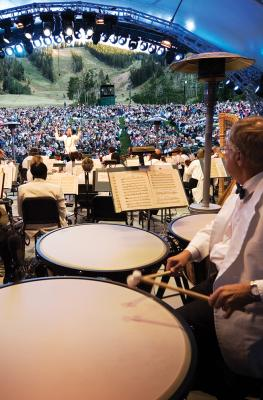View of Symphony from backstage with timpani drum player in foreground and conductor and crowd in the background