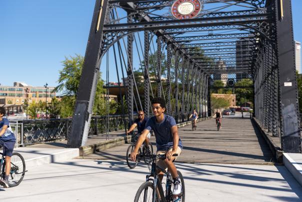 Family Biking Across Wells Street Bridge - Promenade Park