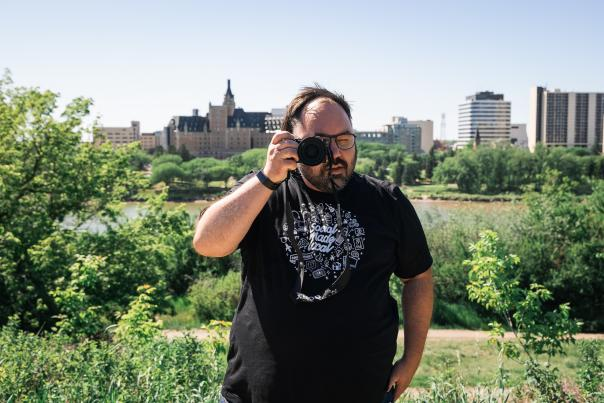 A man with a camera on a river bank with city in the background