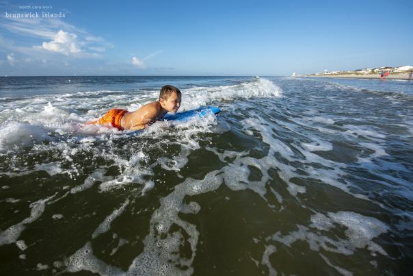 Boy boogie boarding in surf