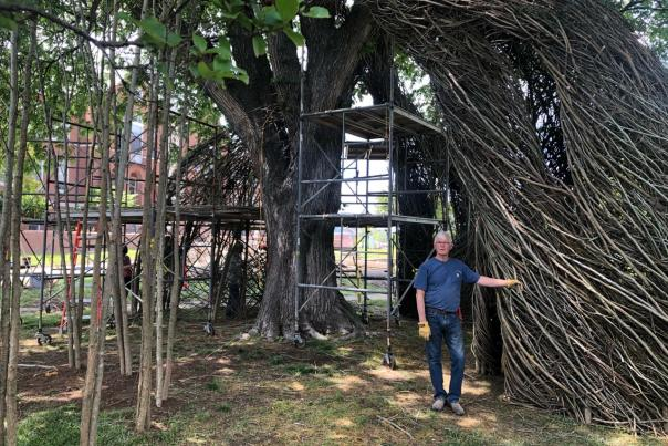 The artist and sculptor Patrick Dougherty stands before his Maryland Hall installation.