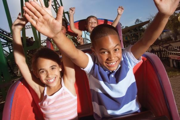 A boy and girl riding a roller coaster at a theme park