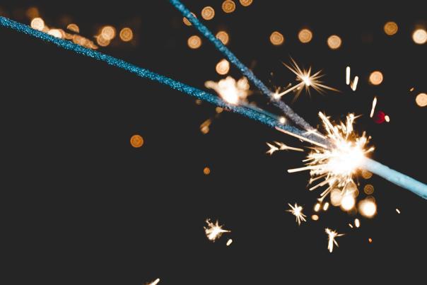 A sparkler being lit against a dark background