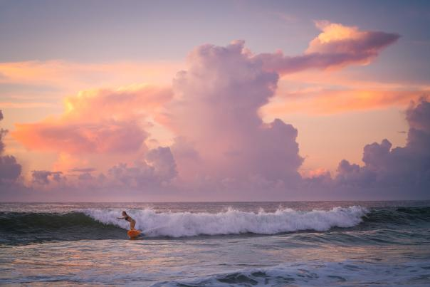 A surfer catches a wave at sunset at Wrightsville Beach