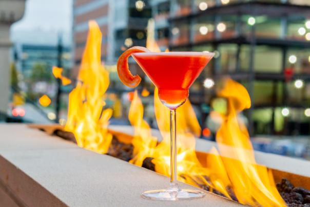 A red cocktail at IDC's patio, positioned in front of an outdoor fire pit in Grand Rapids, MI