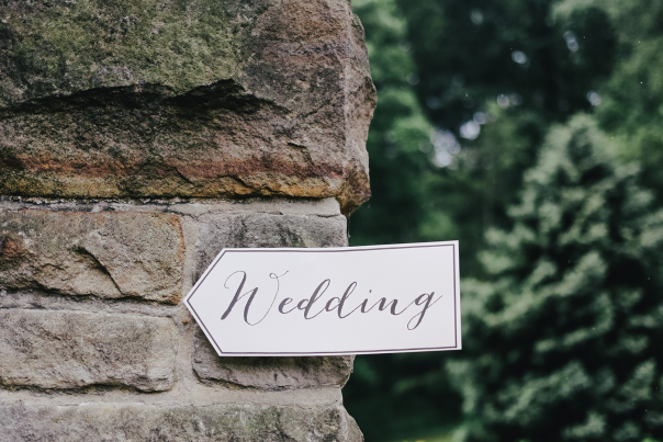"""An arrow shaped sign with the word """"Wedding"""" hanging on a rustic brick wall"""
