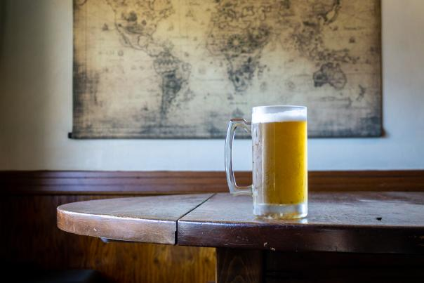 A pint of beer on a table in front of a map of the world on the wall.