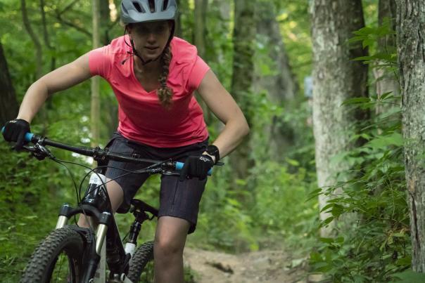 Mountain biker with pink shirt riding through a trail near Grand Rapids
