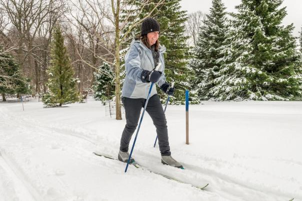 A woman enjoys cross-country skiing on a groomed trail