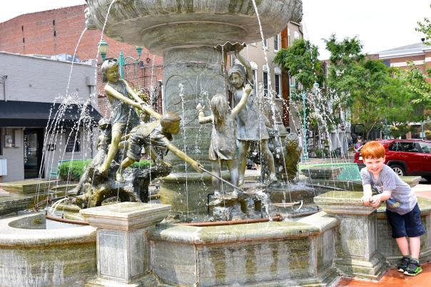boy beside fountain