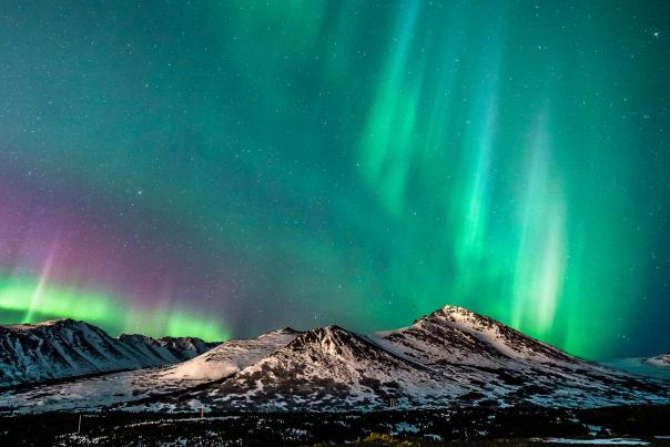 The northern lights, or aurora borealis, shimmer over the snow-covered Chugach Mountains east of Anchorage, Alaska.