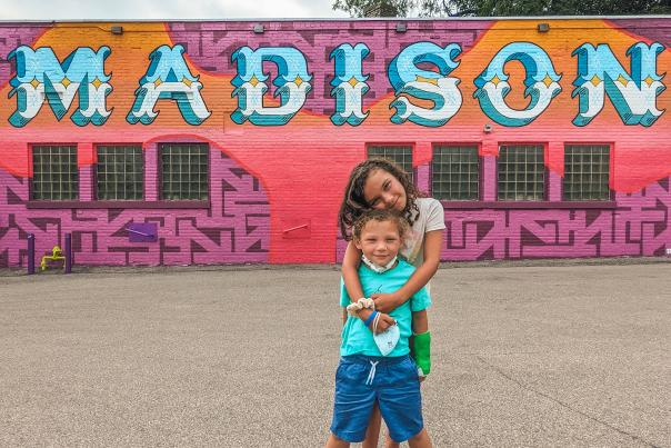 Two kids pose in front of Madison Mural