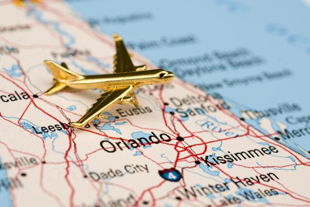gold airplane laying on top of a map of florida