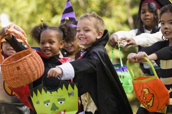 Kids in costumes with trick-or-treat bags