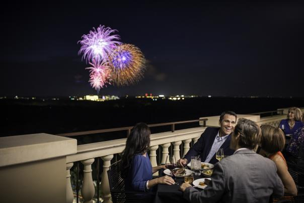 Group of four people watching fireworks and having dinner outside at Capa in the Four Seasons Resort at Walt Disney World Resort