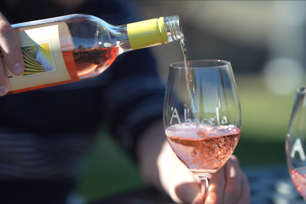 Abacela rosé wine pouring into a glass.